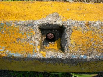 Rusted bolt in yellow concrete wall