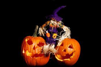 Scarecrow sitting on Pumpkins