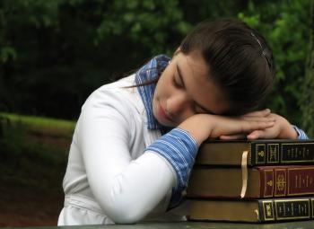 Schoolgirl resting her head on books