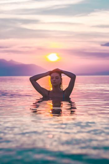 Selective Focus Photo of a Woman Bathing in Body of Water during Golden Hour