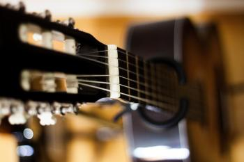 Selective Focus Photo of Black Classical Guitar