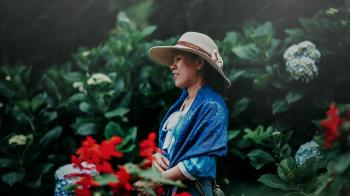 Selective Focus Photo of Woman in Blue Shawl and Brown Sun Hat in the Middle of Garden