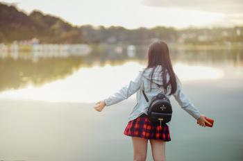 Selective Focus Photography of Girl Near Body of Water