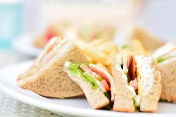 Selective Focus Photography of Plate of Sliced Clubhouse Sandwich