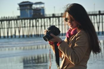 Selective Focus Photography of Woman Holding Her Camera Near Seashore