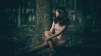 Selective Focus Photography of Woman Wearing Pink Dress Sitting on Tree Roots