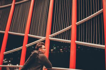 Selective Photography of Man Leaning on White Metal Railings