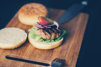 Shallow Focus Photography of Burger Sandwich Served on Brown Wooden Chopping Board