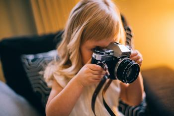 Shallow Focus Photography of Girl Holding a Black and Silver Dslr Camera