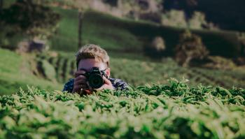 Shallow Focus Photography of Man Holding Dslr Camera