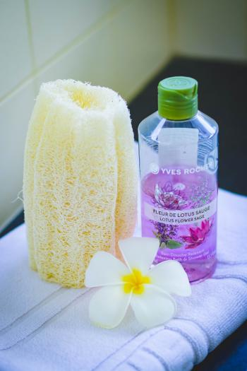 Shallow Focus Photography of Yves Rocher Bubble Bath Bottle on White Towel