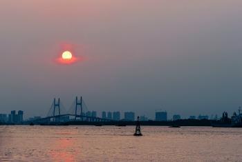Ship Near Brown Bridge Across Sea during Sunset