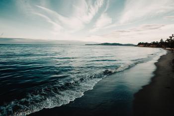 Shoreline Under Blue Sky