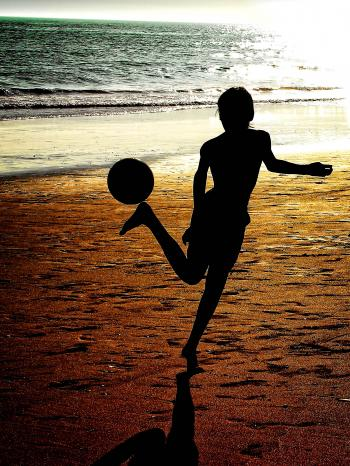 Silhouette of a boy playing soccer