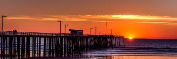 Silhouette of Boardwalk Near Body of Water Under Orange Sunset during Daytime