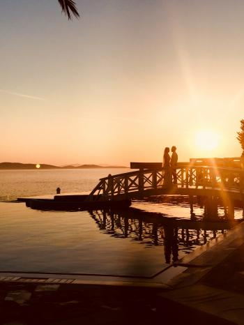 Silhouette of Couple Standing Near Sea Dock at Golden Hour