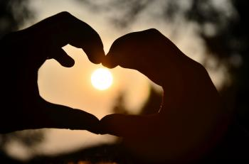 Silhouette of Person Hand Doing Heart Shape during Sunset