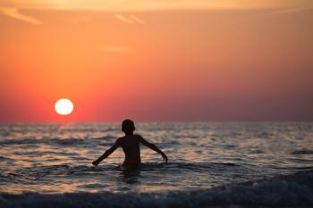Silhouette Photo of Child on Body of Water during Golden Hour