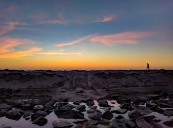 Silhouette Photo of Man Walking on Hill Near Body of Water and Rock Formations