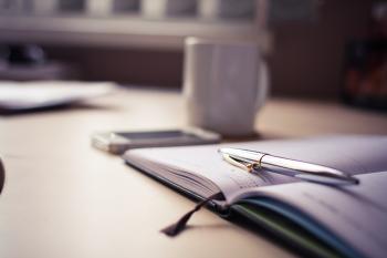 Silver Click Pen on Open Book