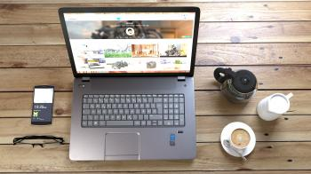 Silver Laptop Next to Coffe Cup Smartphone and Glasses