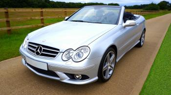 Silver Mercedez Benz Convertible on Brown Concrete Road