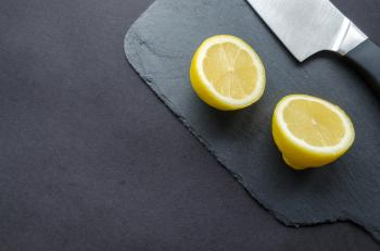 Sliced Lemon Beside Knife on Top of Black Surface