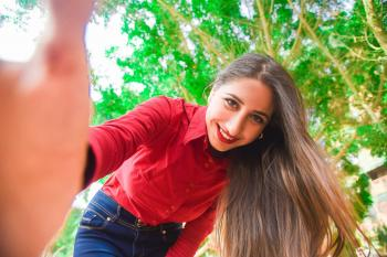 Smiling Woman in Red Shirt and Blue Jeans Taking Selfie Under Green Leaved Tree