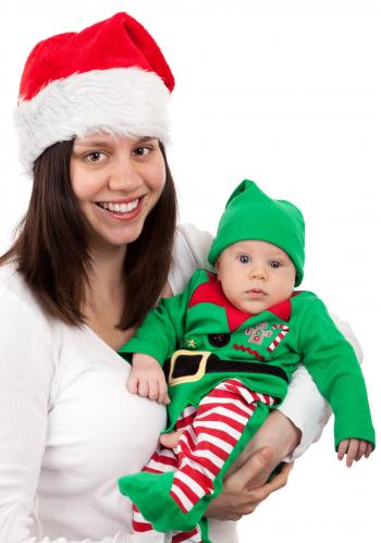 Smiling Woman Wearing Santa Hat Carring Baby Wearing Elf Costume