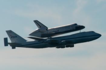 Space Shuttle Endeavour and carrier plane flying over San Francisco Bay - profile view