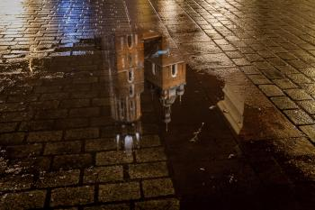 St Mary's Basilica (Kościół Mariacki) reflection in a puddle, Krakow, Poland