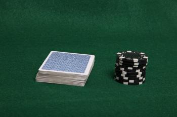Stack of black poker chips and deck of c