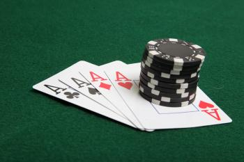 Stack of black poker chips on four aces.
