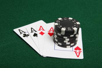 Stack of black poker chips on four aces
