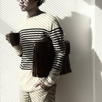 Standing Brunet Person Waring Eyeglasses and White Black Stripe Sweater Holding Mug and Briefcase