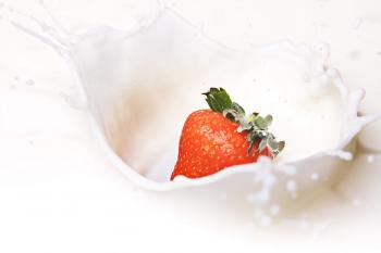 Strawberry dropped in milk