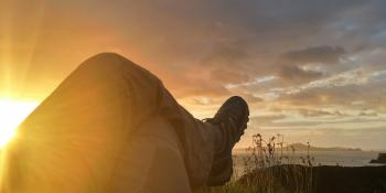 Sun Reflecting on Person Cross Leg Under Cumulus Clouds during Sunrise