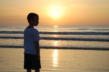 Sunrise at beach with boy