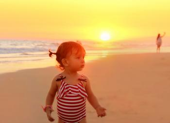 Sweet little girl on the beach at sunset