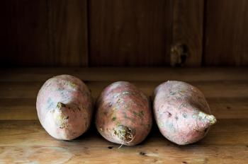 Sweet potatoes on wooden background