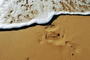 The imprint of a bare foot on the sand