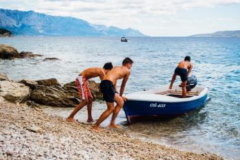 Three Men Pushing Speed Boat on Seashore