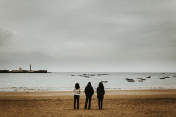 Three Person Standing Near the Seashore
