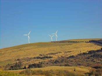 Three White Windmills on Green Field Under Blue Sky