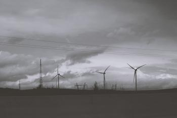 Three Wind Mills Under Cloudy Sky