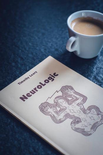 Timothy Leary's Neurologic Book Near White Ceramic Cup