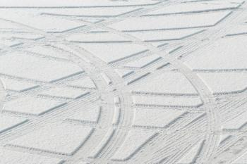 Tire tracks in new snow at a parking lot