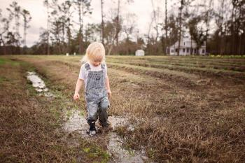 Toddler Wearing Blue Denim Overall Pants Walking on Wet Withered Grass
