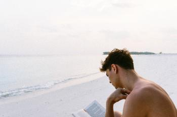 Topless Man Reading Book While Seating at Beach