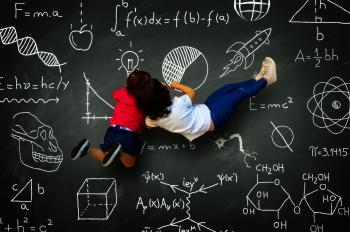 Two little girls writing on a blackboard with science subjects